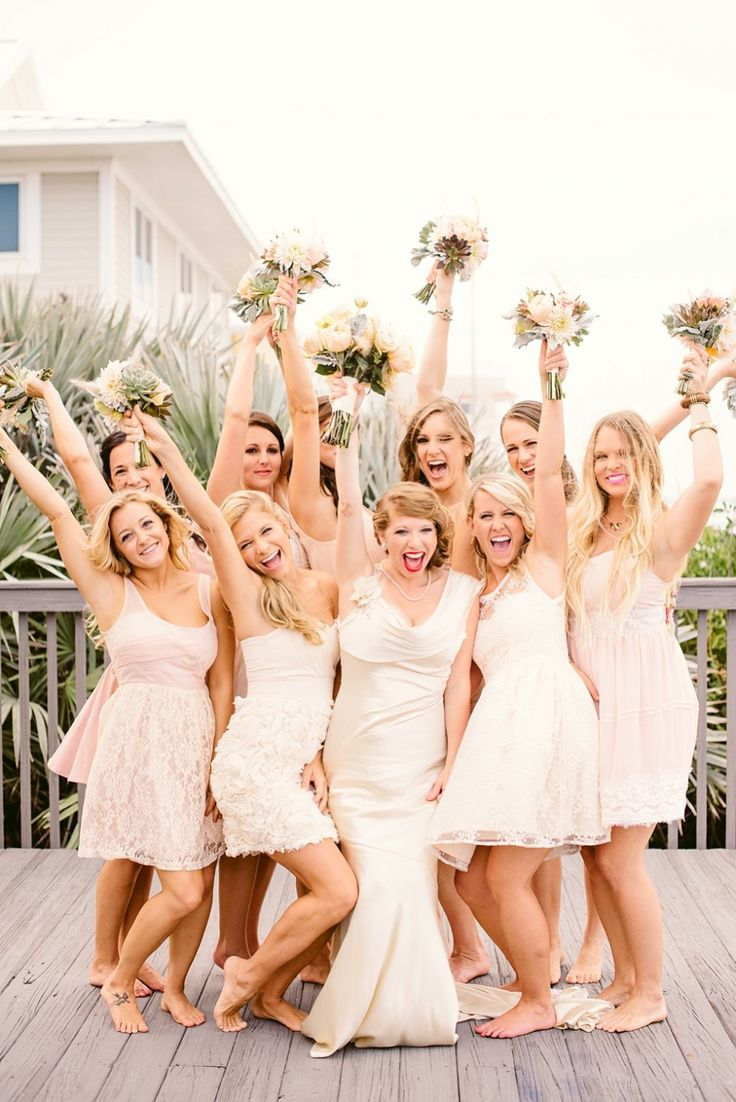 Beachside bride and her bridesmaids raise their sea and sky inspired bouquets of peach and sand , soft pinks, greens & silvery blue.