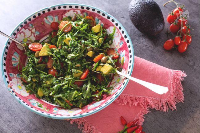 L'insalata con avocado è un contorno fresco ed estivo! Tenera rucola e avocado impreziositi da pomodorini, olive taggiasche e semi di zucca.
