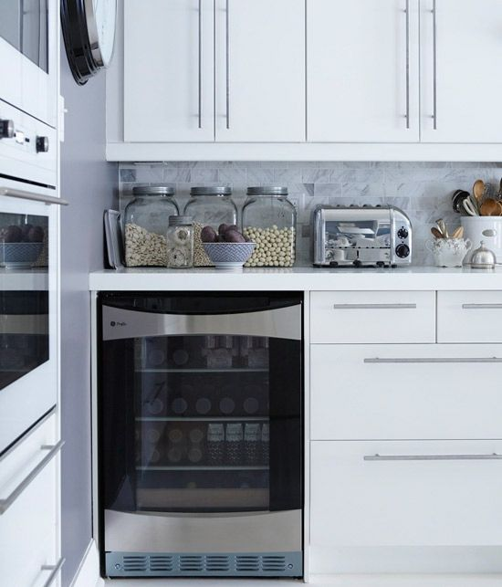 white ikea cabinets, long stainless pulls, white (Corian?) countertop, carrara backsplash