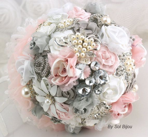 Made Upon Request- This bouquet is available in ANY color scheme  This is an incredibly romantic and chic brooch bouquet. It is a stunning combination of blush pink, silver and white handmade flowers, as well as lustrous pearl and sparkly crystal brooches. This piece, like the rest of my creations, is filled with detail, and has been crafted with quality materials to ensure it can be enjoyed by many generations to come.  The underside has been achieved with a layer of blush pink chiffon and…