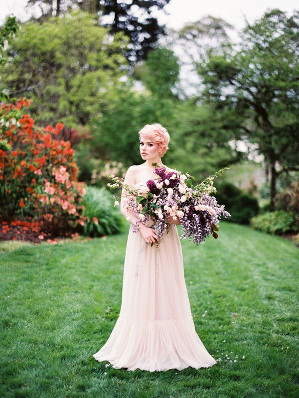 A whole new spin on blushing bride: light pink hair with a pixie cut wedding hairstyle, a pink and purple bridal bouquet and long sleeves blush wedding dress for a modern wedding.