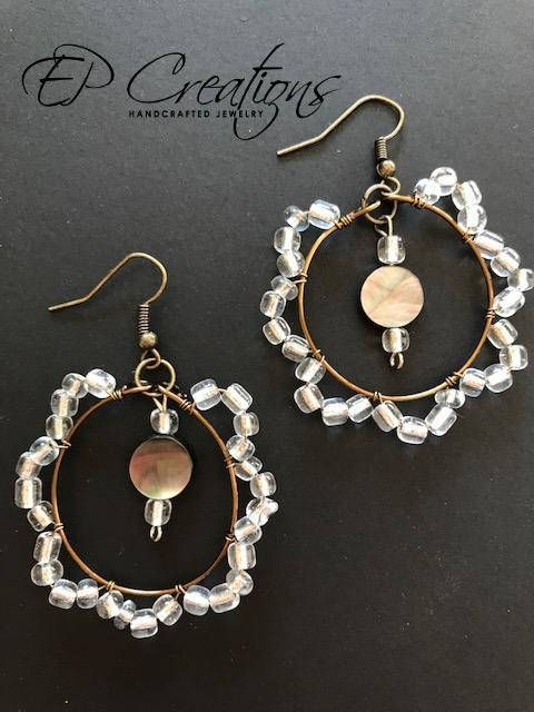 Antique brass wire hoop earrings with clear beads & one mother of pearl beads in the center. They are light-weight and their antique coloring will make the a unique addition for your style. They are simple and very delicate and a perfect accessory for every day. The earring is on a