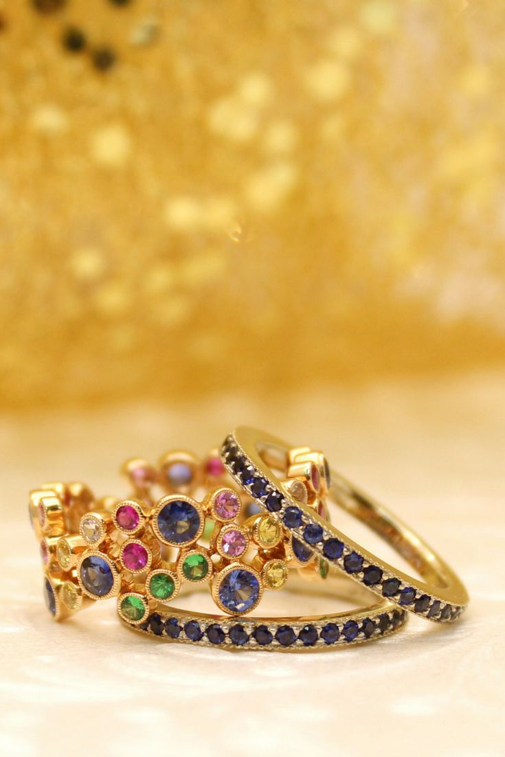 Build your own stackers! The middle@beverleykcollectionbubble ring is 18k gold with multi-coloured precious and semi-precious stones. The two outer sapphire eternity bands are a Wong Ken's Exclusive.⠀#customjewelry#jewelry #coloredstones#preciousstones #semipreciousstones#gold#bezel #holidays#womensfashion #jewelrydesigner#calgarybride #womensjewelry#sparkle#sapphire