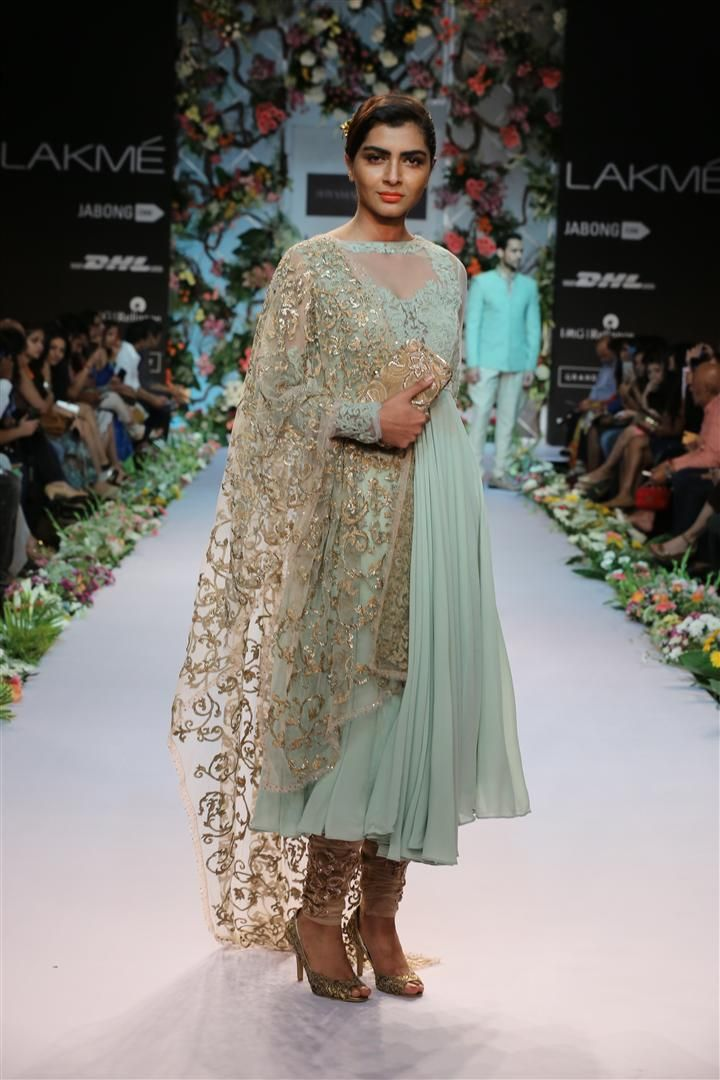 a dusty green panelled top with a cutout sheer back yoke. The delicate thread embroidery on the sheer net enhances the intricate detail of the bodice. Adding a zardozi filled net chudidar and a floral pita work dupatta gives it an elegant yet subtle look.