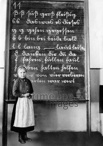 Schülerin vor einer Tafel, 1930 Timeline Classics/Timeline Images #30er #schwarzweiß #Fotografie #photography #historisch #historical #traditional #traditionell #retro #nostalgic #Nostalgie #Schule #School #Schüler #Lernen #Studieren #Bildungseinrichtung #Unterricht #Schulzeit #Ausbildung #konzentriert #Mädchen #Tafel #Schiefertafel #üben #schreiben #Hausaufgabe #Schulaufgabe #Klassenzimmer #Schrift #Sütterlinschrift #Sütterlin