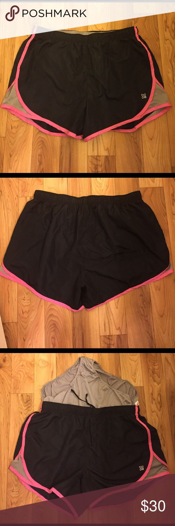 Workout shorts Black polyester workout shorts, with a pink accent.  Built-in mesh liner, and mesh sides for ventilation. Small pocket on the inside for keys. From Lady's Footlocker. Shorts