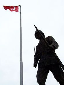 Photographie en contre-plongée d'une statue en bronze représentant un soldat tenant un fusil et un sabre. Un drapeau turc au sommet d'un mat est visible à l'arrière-plan.