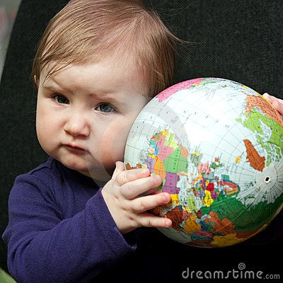 Portrait of cute baby girl or toddler holding colorful globe of world.