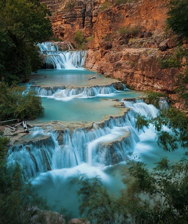 Havasu Creek's blue-green water tumbles over waterfalls in Havasu Canyon.
