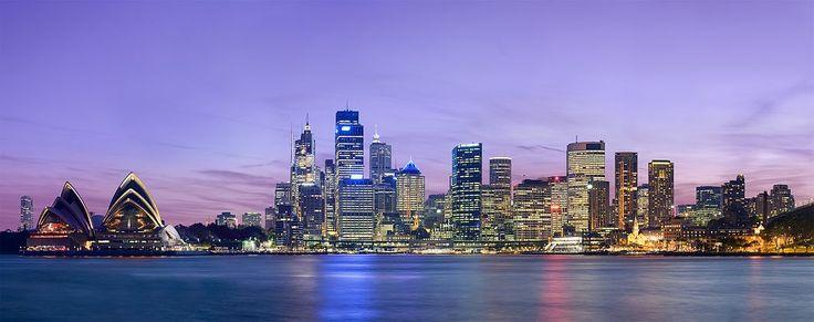 Panorama Sydney za soumraku, metropole svazového státu Nový Jižní Wales, kterou vroce 1788 založil admirál Arthur Phillip jako britskou vězeňskou kolonii okolo zálivu Port Jackson. Spopulací 4,9milionů obyvatel Sydney představuje nejlidnatější město vAustrálii. Vlevo stojí operní dům navržený dánským architektem Jørnem Utzonem anapravo se tyčí mrakodrapy centrální obchodní oblasti.
