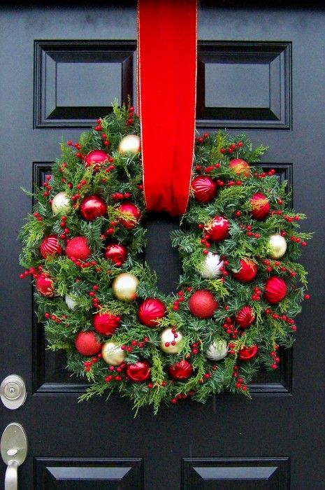 Decorate your wreath with red and gold ornaments and berries.