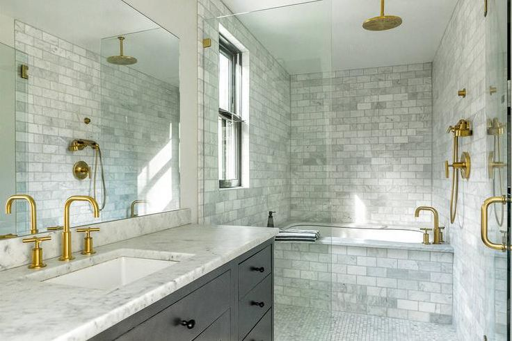 Gold and gray bathroom features a large seamless glass shower accented with brass hardware a