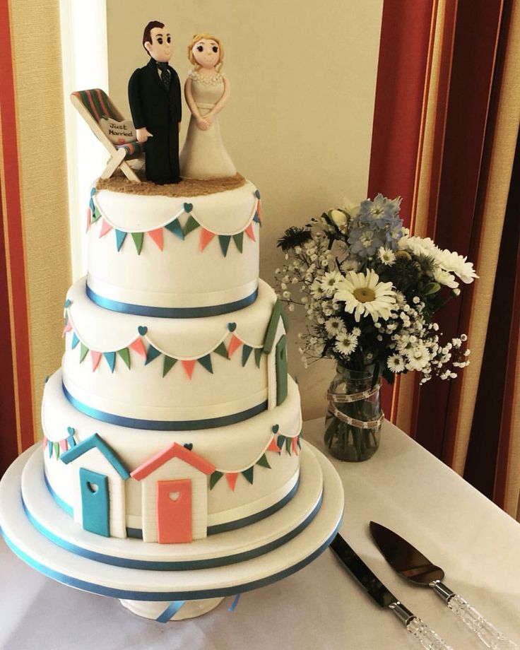 Seaside wedding cake. Beach huts and bunting cake by Creative Cakes by Louize (Scarborough, UK).