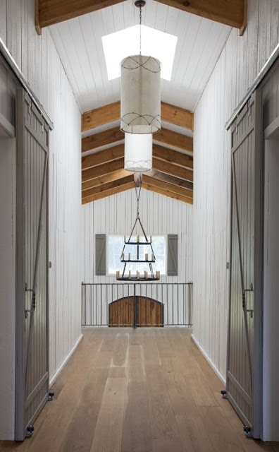 Barn doors accent this bright hallway. Natural light makes this space a great experience.