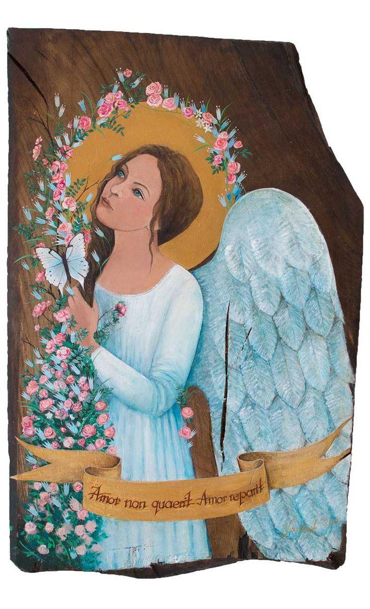 """""""Biały Anioł"""" jest aniołem przeznaczonym na prezent ślubny. Anioła namalowałam na kawałku starej, grubej (4 centymetry) deski dębowej. Pęknięcia i nierówności wynikają ze struktury drewna. Praca została wykonana farbami akrylowymi, następnie pokryta woskiem antycznym. Na szarfie widnieje napis : """"Amor non quaerit, Amor reperit"""" (Miłość nie szuka, miłość znajduje)."""