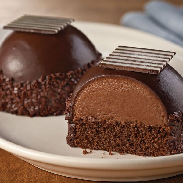 Chocolate Bombe Cakes have a layer of chocolate caramel mousse on chocolate devil's food and covered with dark chocolate ganache