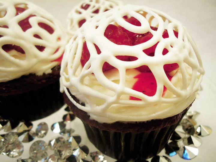 """Chocolate Cupcakes with a White Chocolate frosting topped with Fresh Raspberries and a White Chocolate dome"""