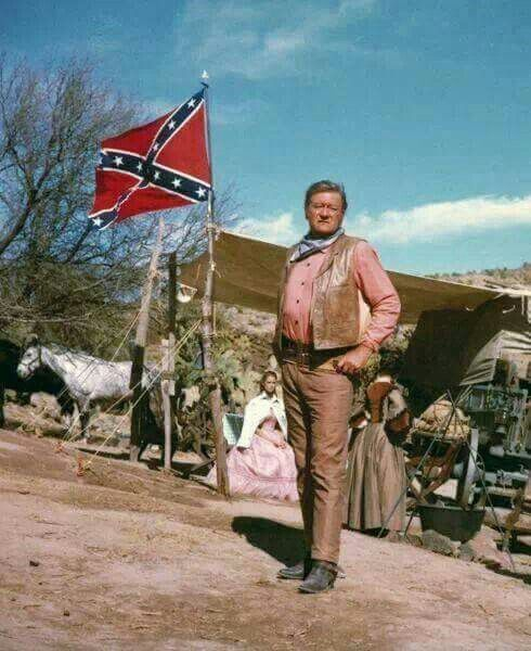 John Wayne poses with Confederate Flag in the background.