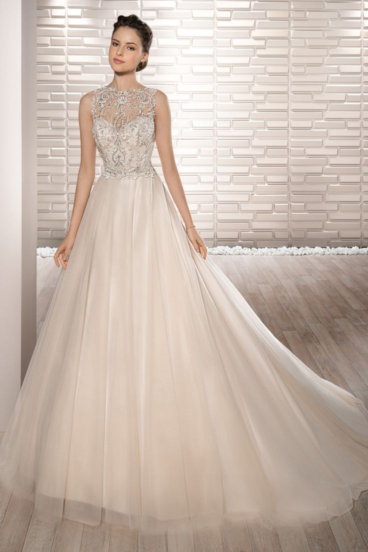 Style 679  Glamour and a little glitz make up this dreamy sleeveless ball gown with exquisite beading on the bodice, sheer Bateau neckline and dramatic illusion back with button closure.  The Tulle skirt flows into a Chapel length train.