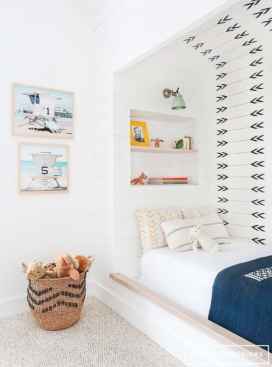 Fabulous kid's bedroom features a nook filled with a bed situated under a built-in niche bookcases illuminated by a mint green sconce.