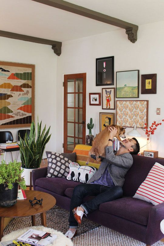 seems like a happy room-----love the purple sofa, art and greenery and dog of course