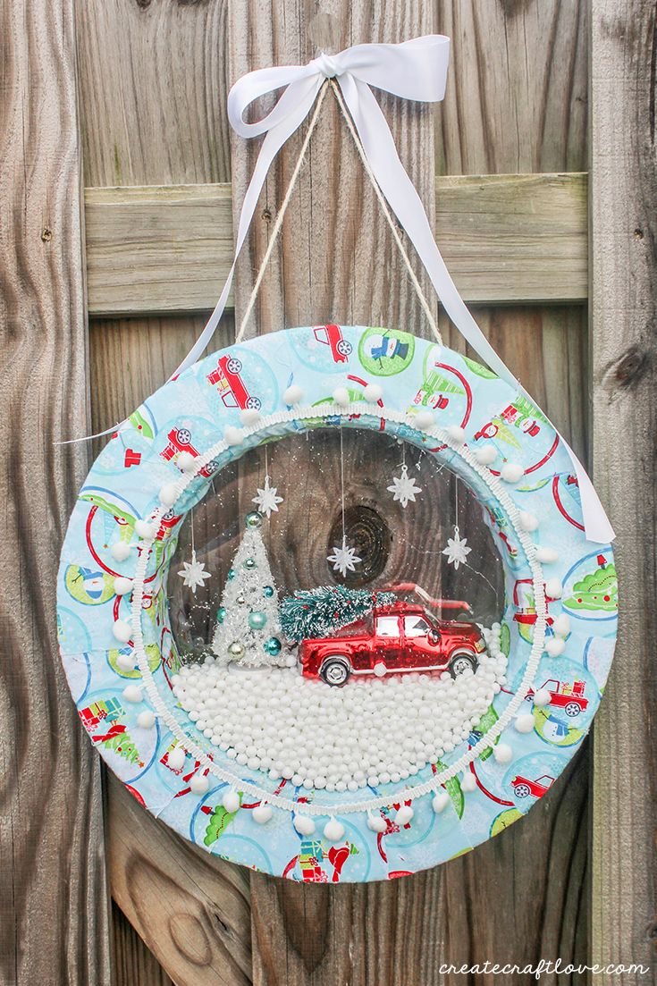 Hang your snow globe wreath with twine and ribbon to display for holiday guests!