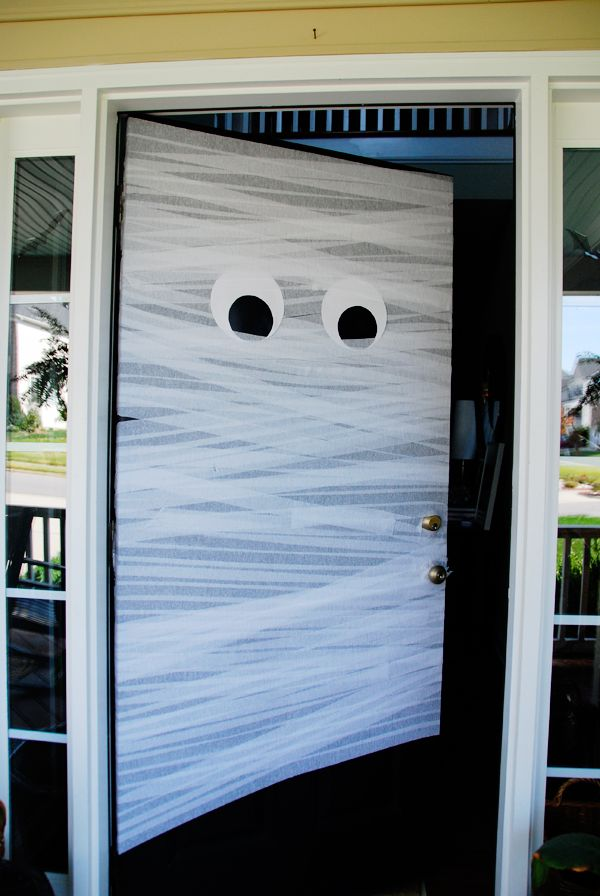 DIY Halloween Front Door Mummy   - 2 rolls white streamers  - 2 eyes made with white & black paper  - wrap door, taping on the inside of the door.