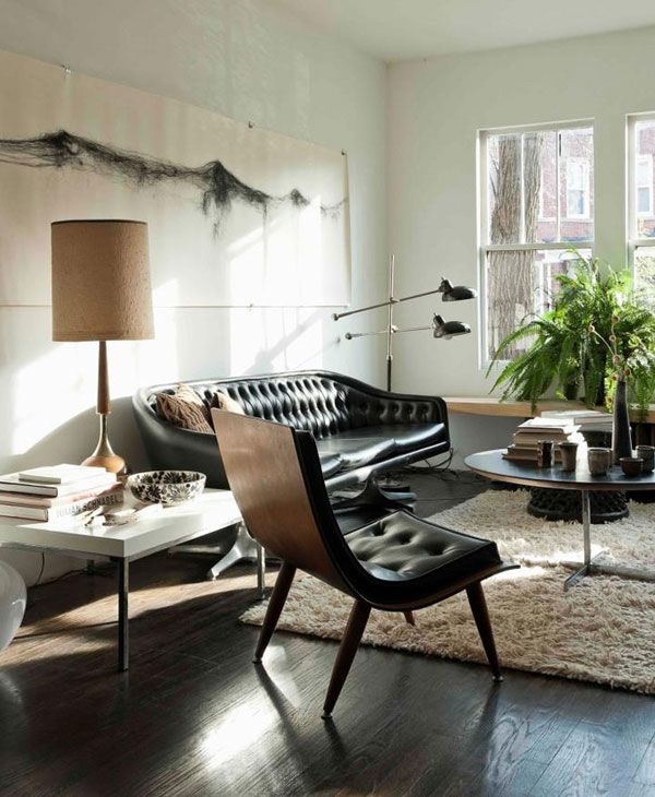 Sofa Slipcovers This mid century modern living room features a black vintage leather sofa shag rug and a wood and leather side chair over sized lamp shade and some