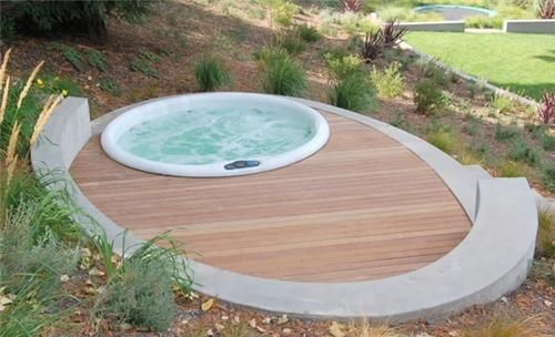 deck concrete, wood with sunken hot tub on sloping lot