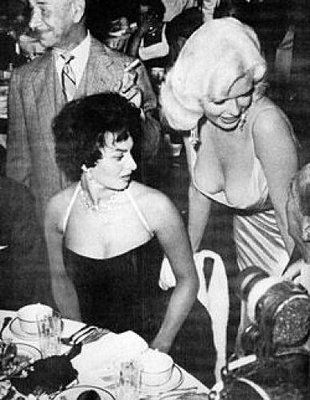 sophia loren, gazing in unabashed horror at jayne mansfield's sweater puppies