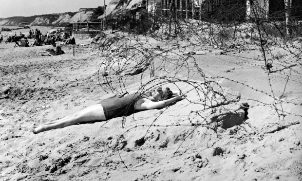 A woman sunbathes on a wartime bank holiday surrounded by barbed wire on the beach at Bournemouth, 1944. Topical Press Agency/Getty Images