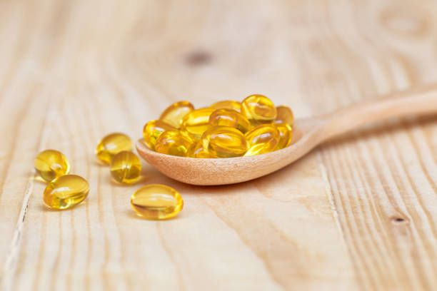 fish oil capsules with omega 3 and vitamin d on spoon wood with