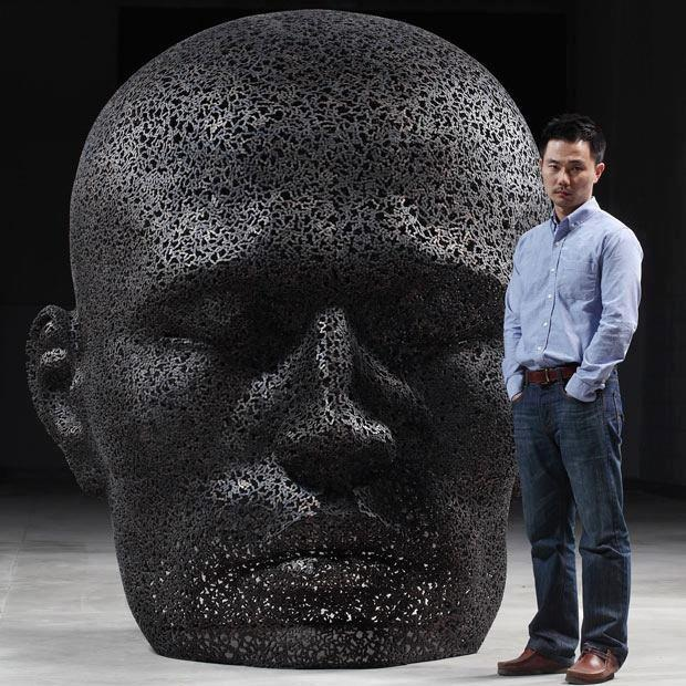 "South Korean artist Seo Young Deok poses with one of his sculptures, ""Nirvana,"" made from bicycle chains."