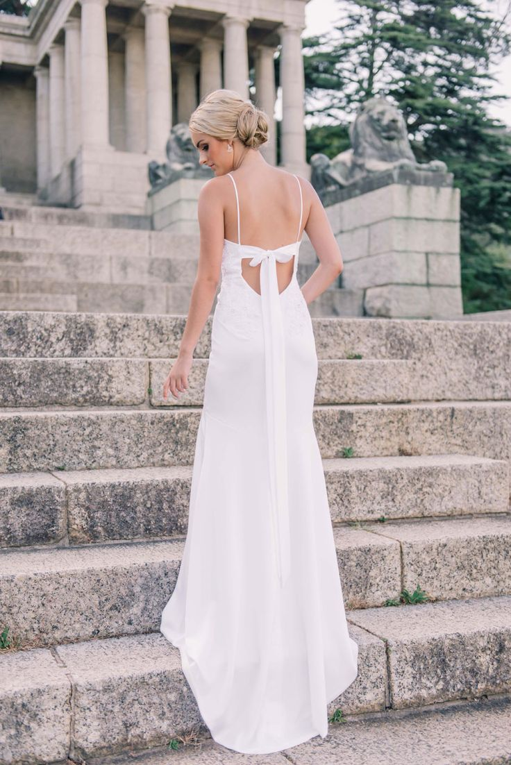 A soft flowing natural white infinity satin sheath style gown with spaghetti straps and a zip closure. The dress features beaded lace applique and alow back secured witha bow sash.