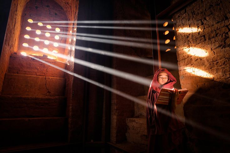 Young Monk finds a perfect light source to read his book inside of his pagoda – Old Bagan, Burma | Like and Mention