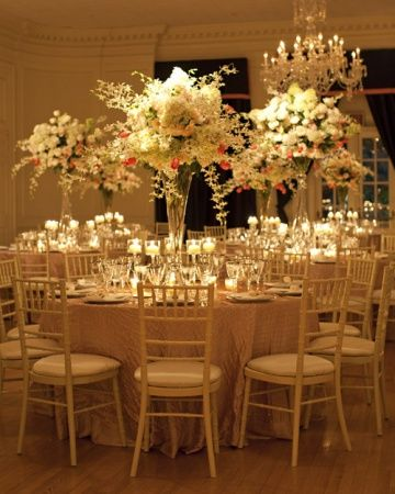White Centerpiece in tall glass vase.orchids,cafe au lait dahlias,pink tulips & blush akito roses