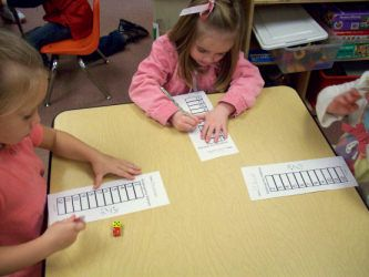 "First Grade Yahtzee - ""This game is so funny to see how excited the kids get. All they have to do is roll 2 dice and cross out the sum. They keep going until they have crossed out all of the numbers. They learn the hard way how hard it is to roll a 2 or a 12."" -- Could do this in 2nd grade with two-digit addends."