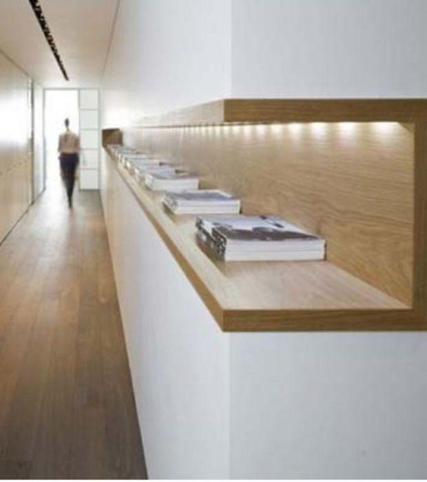 Des tablettes encastrées dans un long corridor pour y poser des livres, magazines, etc