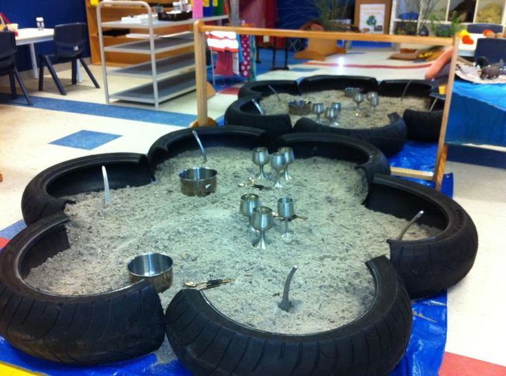 Indoor sandpit on top of a tarp - used tires, sliver cups and bowls in front of a mirror - beautiful and inviting! - at Pelican Childcare Heatherton ≈≈