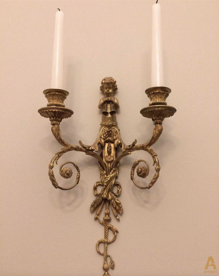 """Пара настенных канделябров на две свечи украшенные фигурой """"Путти играющих на двух флейтах""""."""