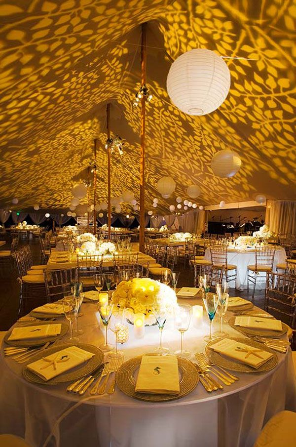 party lighting ideas. gobo lights project yellow foliage along the cieling of this outdoor wedding tent while paper lanterns hover over reception tables party lighting ideas
