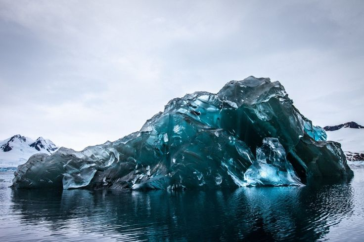 An extremely rare flipped over iceberg in Antarctica gives us a look at the beautiful blue hues of water.  Yes, water has a color.  It is not the color of the sky reflected.  It's natural color is a turquoise blue like seen here.  It's rare to see water ice dense enough to show those hues.  Gorgeous!