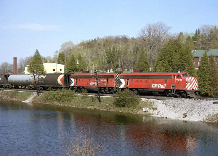An A-B pair of matching F-units in CP's Action Red, FP7 4031 and F7B 4433, head west on the Galt Sub through Campbellville passing the ponds. Also of note are the early design cylindrical hoppers behind, bracketing a grey pressure-flow covered hopper. This scene is a difficult shot today due to the foliage growth.  The remaining GMD F-unit fleet on CP only had a few more years to go, before being retired en masse in 1982 (although a few remained in Montreal commuter service before going to…