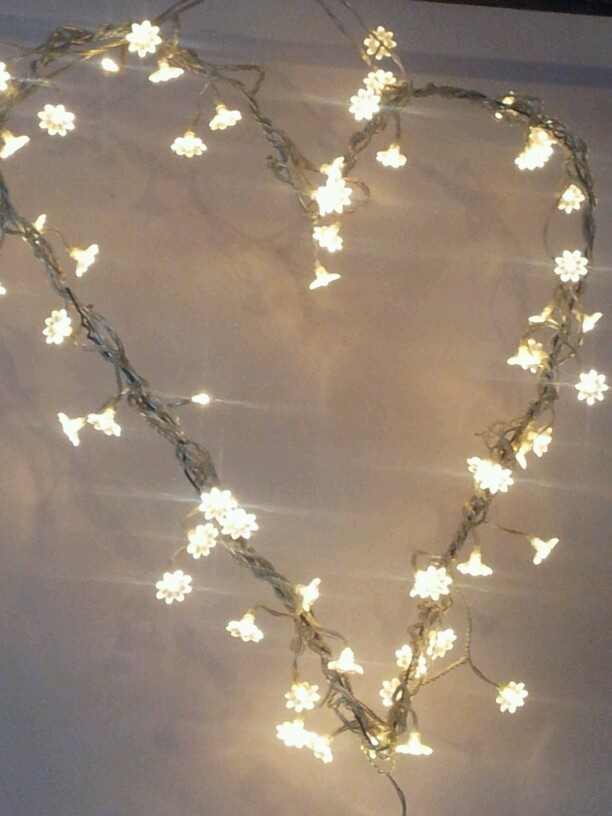 DIY: a wire coat hanger shaped into a heart and wrapped around with fairy lights. Cute!