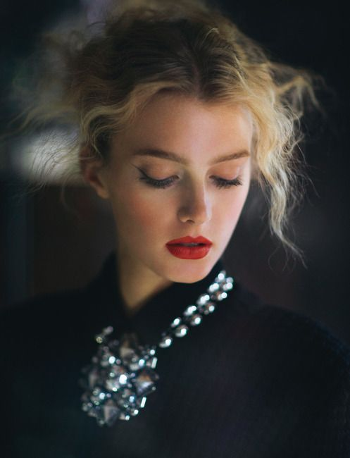 frizzy hair, red lips and statement necklace.