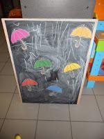 Op het krijtbord / white board hangt de kleuterjuf enkele paraplu's. De kleuters tekenen de regendruppels onder de paraplu's. Zo leren ze rechte lijnen te trekken.