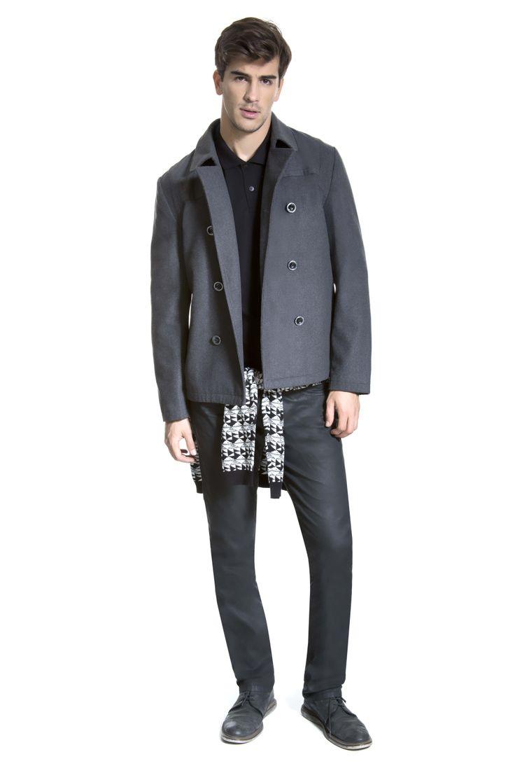 Camisa polo preta sobreposta por casaco de lã cinza, tricô étnico na cintura e calça resinada preta.