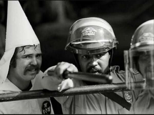 """""""Can you say Ironic? A black policeman protects a KKK member, as protesters were closing in on them at a rally in Austin, Texas 1983."""""""
