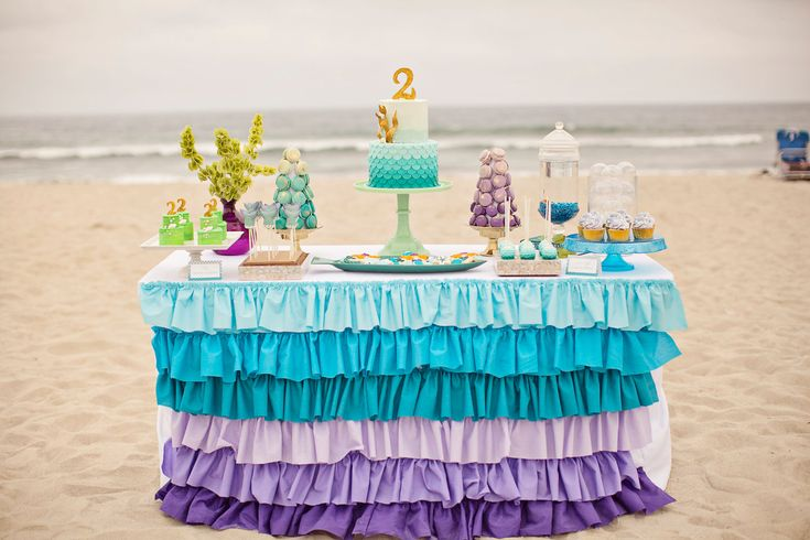 Ruffle Tablecloth that is being used for cake table.  Centerpiece will be the cake as pictured in this picture.  Next to that will be mason flower jars, 2 hurricanes with sand and shells.  2 pedestal hurricanes with water, blue glass rocks and shells.  Party favors - girls and boys on each side. Shells scattered throughout. Possibly cupcakes?  Any glass colored balls I can put in vase?
