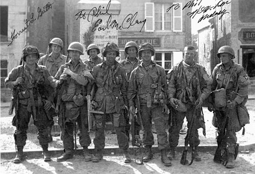 "E Company paratroopers in the square at St. Marie-du-Mont. (Front, L-R) Forrest Guth, Frank Mellet, David Morris, Daniel West, Floyd Talbert and CT Smith pose with infantrymen from the Army's 4th Division.  Photo by Walter ""Smokey"" Gordon, June 7 1944."